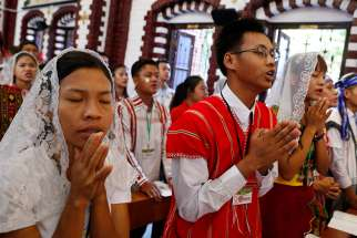 Young people pray as Pope Francis celebrates Mass with youths at St. Mary's Cathedral in Yangon, Myanmar, Nov. 30.