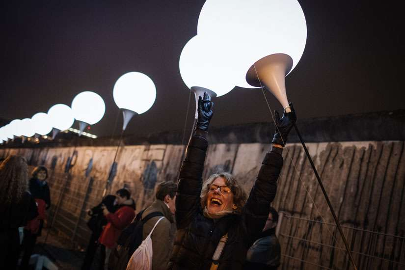 A woman celebrates as she awaits the release of balloons into the sky along the former path of the Berlin Wall in Berlin Nov. 9. Commemorating the 25th anniversary of the fall of the Berlin Wall, Pope Francis said the sudden end to the division of Europe was prepared by the prayers and sacrifice of many people, including St. John Paul II.