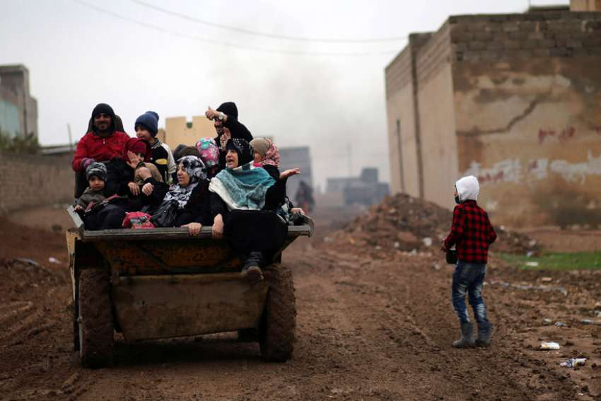 Displaced Iraqis ride in a truck Dec. 1 as they flee the Islamic State stronghold of Mosul.