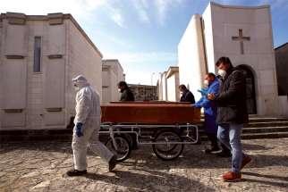 Funeral service workers transport a coffin of a victim of COVID-19 in Cisternino, Italy.