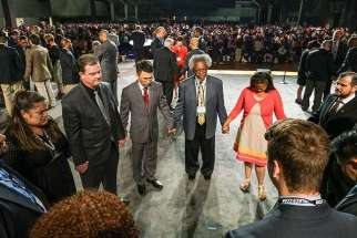 Southern Baptist Convention leaders pray together on the stage during the National Call to Prayer for Spiritual Leadership, Revived Churches and Nationwide and Global Awakening during the annual meeting of the Southern Baptist Convention on Tuesday, June 14, in St. Louis.
