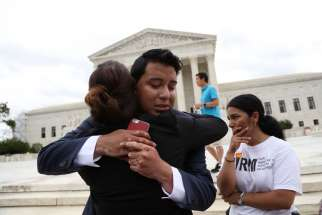 Advocates for immigration reform react June 23 outside the U.S. Supreme Court in Washington after the justices issued a 4-4 split ruling on President Barack Obama's executive actions on immigration, leaving in place a lower court ruling that blocked Obama's policies