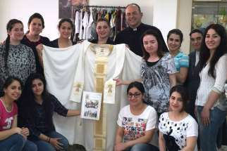 Iraqi refugee women who fled Islamic State group violence in their homeland pose for a photo in Amman, Jordan, in early June. The Chaldean Catholic women sent the hand-sewn mantle to Pope Francis and asked him to pray for them and for peace in their country.