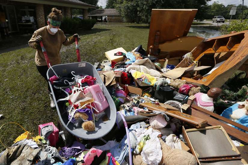 Melissa Gouda removes flood damaged items out of a friend's house in St. Amant, La., Aug. 21. Historic flooding in southern Louisiana killed at least 13 people and damaged an estimated 60,000 homes, said state officials. At least 102,000 people have registered for federal recovery assistance.