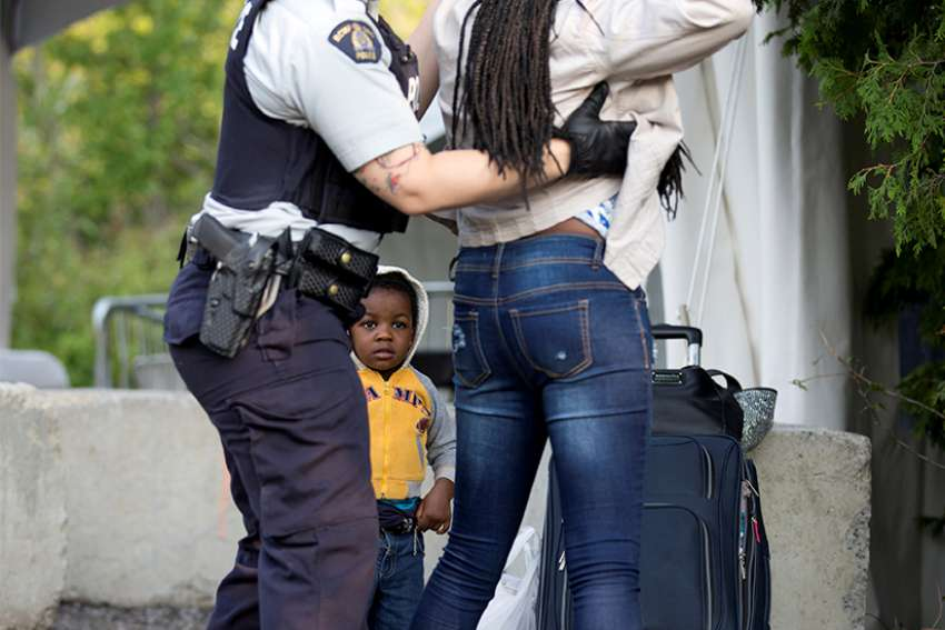 Two-year-old Evanston, whose family stated they are from Haiti, watches as a Royal Canadian Mounted Police officer pats down his mother before the two cross the U.S.-Canada into Quebec Aug. 29, 2017.