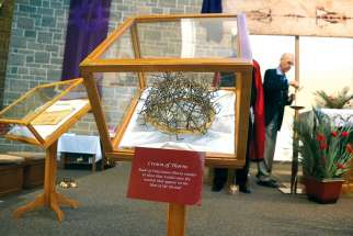 The replica of the Crown of Thorns shows a cap of Palestinian thorns that would have created wounds consistent with those on the Shroud. In the background, the Shroud replica hangs over the altar.