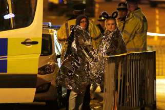 Two women wrapped in thermal blankets stand near Manchester Arena in England where U.S. singer Ariana Grande had been performing May 22. At least 22 people, including children, were killed and dozens wounded after an explosion at the concert venue. Authorities said it was Britain's deadliest case of terrorism since 2005.