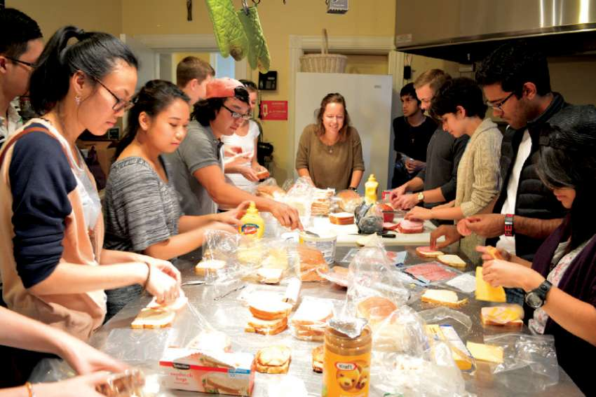 Catholic students at Toronto's Newman Centre make sandwiches as part of a street patrol formed on campus.