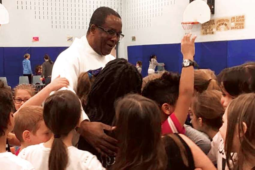 At Saints-Martyrs-Canadiens in Cambridge, Fr. Lourdy Dorismond shepherds the children. The parish has plans to increase children's catechesis and its ties to area Catholic schools.