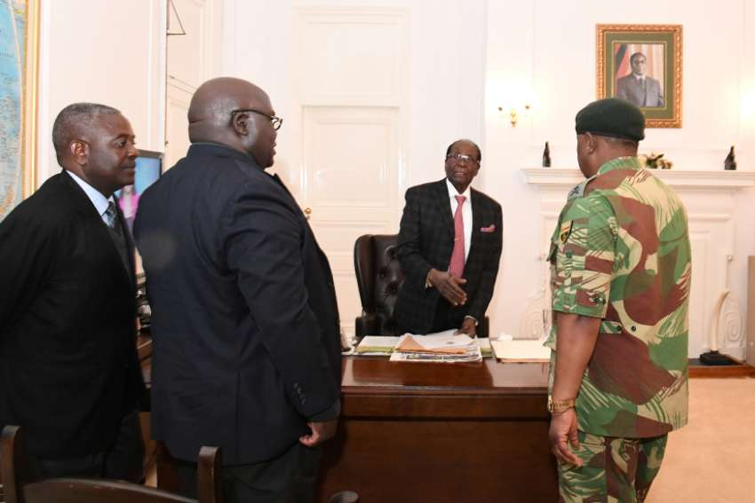 President Robert Mugabe, center, meets with Gen. Constantino Chiwenga, right, Nov. 19 at the State House in Harare. Looking on is Brigadier Gen. Happyton Bonyongwe, minister of justice, and Father Fidelis Mukonori, parliamentary liaison officer for Harare Archdiocese.