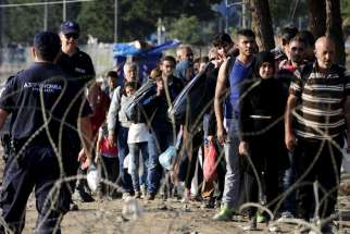 Migrants enter Macedonia near Gevgelija after crossing the border with Greece Sept. 1. Catholic aid agencies have urged Europeans not to turn against migrants seeking refuge from Syria and other countries, in what media reports describe as the continent's greatest refugee movement since World War II.