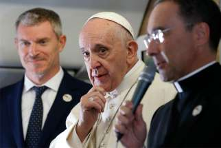 Pope Francis is pictured as he greets journalists aboard his flight from Rome to Maputo, Mozambique, Sept. 4, 2019. The pope will also visit Madagascar and Mauritius through Sept. 10. At left is Matteo Bruni, new director of the Vatican Press Office, and at right Msgr. Mauricio Rueda, papal trip planner.