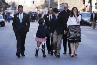 The family of Boston Marathon bombing victim Martin Richard walk along Boylston Street April 15 with a clergyman and Boston Mayor Marty Walsh, left, following a ceremony at the site of the second bomb blast on the second anniversary of the bombings. Mart in's father, Bill, smiles as he walks behind his daughter, Jane, second from left, son Henry and wife Denise, right. Young Martin was killed in the attack, just a few days shy of his ninth birthday.