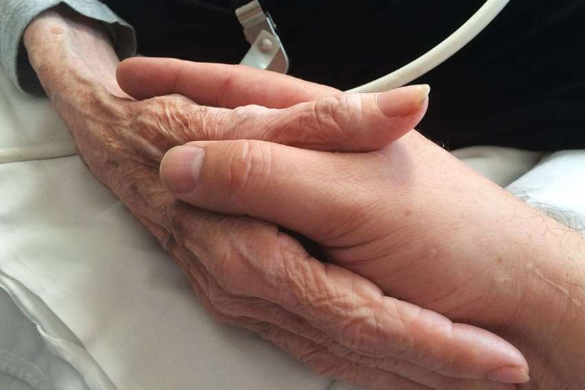 A son holds his mother's hands at a hospice care facility moments before her death from ovarian cancer in 2015.