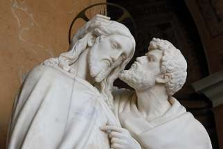 Judas kisses Jesus, an act of ultimate betrayal.