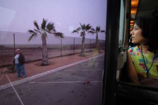 Yelda Cortez of the U.S. bishops' Migration and Refugee Services office, looks out the window of a bus as it makes its way along the U.S.-Mexico border fence.