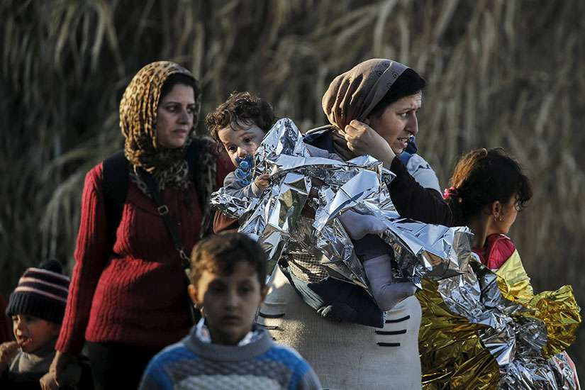 A Syrian refugee carries her child in a thermal blanket as refugees and migrants arrive on an overcrowded boat on the Greek island of Lesbos, 2015. CNEWA's $150 million contributed to Iraq and Syria in 2015 was only second to the United Nations'.