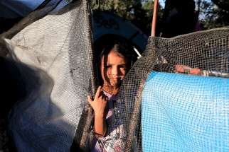 A girl looks out from a makeshift tent Sept. 17 at a camp for refugees and migrants on the island of Lesbos, Greece.