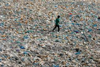 A boy walks over a drainage channel littered with garbage in Karachi, Pakistan, on Earth Day April 22, 2020.