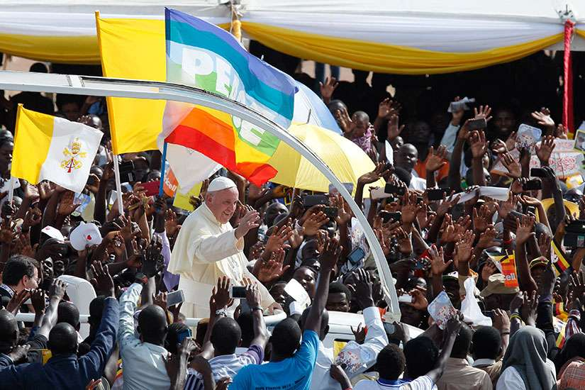 The Vatican flag and a peace banner are seen as Pope Francis greets the crowd as he arrives for a meeting with young people at the Kololo airstrip in Kampala, Uganda Nov. 28.