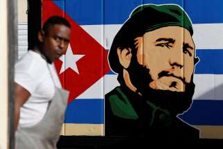 An employee of a state-owned candy store looks outside near a painting depicting Cuba's former President Fidel Castro, following the announcement of Castro's death, in Havana, Nov. 27.