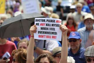 A woman holds up a sign during a rally against assisted suicide on Parliament Hill in Ottawa in 2016.