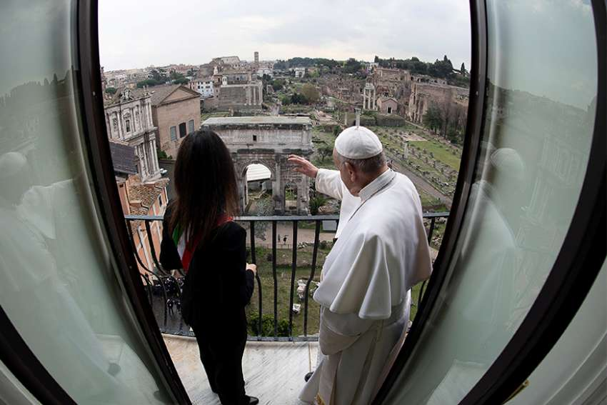 Pope Francis waves from a balcony alongside Rome Mayor Virginia Raggi during a visit to City Hall March 26, 2019.