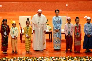 Pope Francis and Aung San Suu Kyi, state counselor and foreign minister of Myanmar, are picture with children before a meeting of government authorities, members of civil society and the diplomatic corps at the Myanmar International Convention Center in Naypyitaw, Myanmar, Nov. 28.