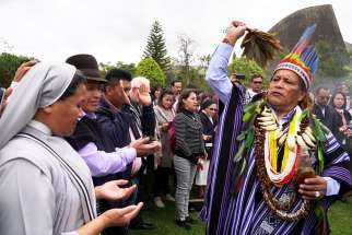 Isidoro Jajoy, a shaman from Colombia's Inga tribe, blesses people in Bogota Aug. 14, 2019, during a preparatory meeting for the October Synod of Bishops for the Amazon.