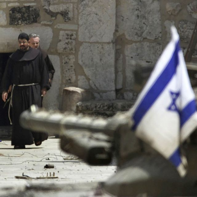 The gun on an Israeli tank points at the door of the Church of the Nativity in Bethlehem, past two Franciscan friars, during the 2002 occupation of the church by Palestinian gunmen.