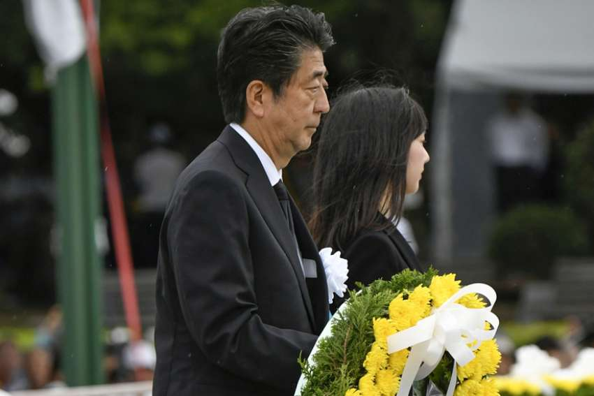 Japanese Prime Minister Shinzo Abe carries a wreath for the victims of the 1945 atomic bombing at Peace Memorial Park in Hiroshima, Japan, Aug. 6, 2019. The cermony marked the 74th anniversary of the bombing.