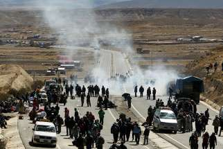 Bolivian miners clash with police Aug. 11 during a protest along a road in Mantecani. Large-scale mining and extractive operations are failing to deliver economic benefits while causing environmental damages and human suffering throughout Latin America.