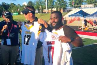 Douglas coach Willis May, left, and St. Matthews Tigers coach Jean Guillaume exchange school jerseys with number 17 to commemorate the 17 victims of the Stoneman Douglas high school shooting.