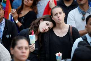 Women hold candles during a June 13 vigil in Los Angeles for the victims of the mass shooting at the Pulse gay nightclub in Orlando, Fla. A lone gunman, pledging allegiance to the Islamic State terrorist group, killed 49 people early June 12 at the nightclub.