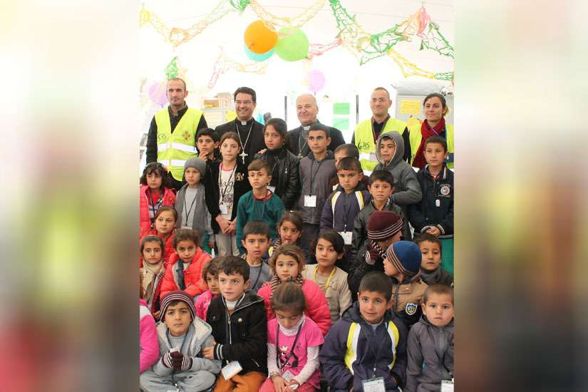 Displaced Iraqi Yezidi children greet Catholic Relief Service workers and a delegation of the U.S. Conference of Catholic Bishops, led by Bishop Oscar Cantu during a visit to Shariah Collective, Iraq, Jan. 17.