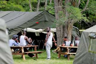 "Refugees seeking asylum are seen near the border in Lacolle, Quebec, Aug. 10. Jesuit Father Michael Czerny, undersecretary of the migrant and refugee section of the Vatican's Dicastery for Promoting Integral Human Development, said Sept. 4 the Vatican believes countries must guarantee ""adequate legal frameworks and reliable pathways to prevent migrants from becoming victims of human trafficking."""