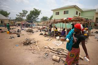 A woman carries a child through a camp in the state of Benue, Nigeria, April 11. The Catholic Diocese of Makurdi and others condemned the killings of two priests and 17 parishioners of St. Ignatius Catholic Church in the state.