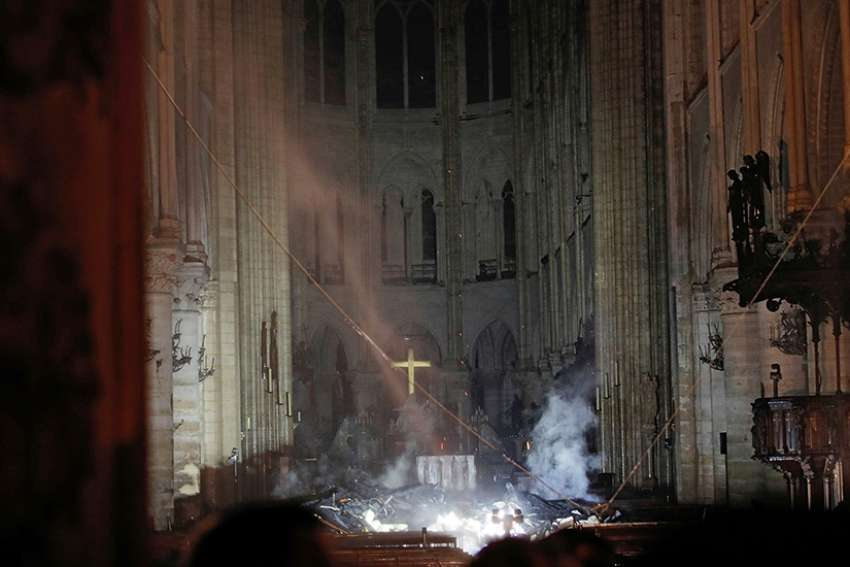Smoke rises around the altar inside Notre Dame Cathedral in Paris as a fire continues to smolder early April 16, 2019. Officials said the cause was not clear, but that the fire could be linked to renovation work.