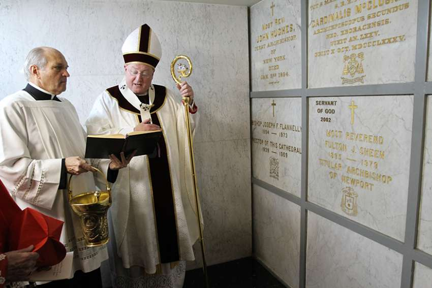 Then-Archbishop Timothy M. Dolan of New York prays at the tomb of Archbishop Fulton J. Sheen at St. Patrick's Cathedral in New York City in 2009 after celebrating a memorial Mass for the prelate.