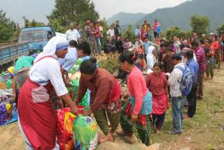 A member of the Missionaries of Charity helps distribute relief items to earthquake victims May 16 in the mountains overlooking Kathmandu Valley in Nepal. Toronto donors faced tough decisions when it came to giving to disaster relief, local charities and fundraising initiatives.