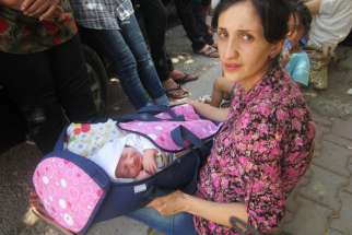 An Iraqi Christian refugee holds a 12-day-old baby in Ankawa, Iraq, Aug. 7.