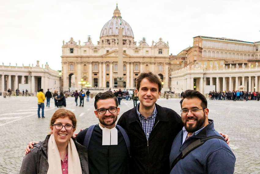 Katie Prejean-McGrady, De La Salle Christian Brother Javier Hansen, Chris Russo and Nick Lopez, some of the young adults from the United States participating in the Vatican's pre-synod meeting, posed March 21 in front of St. Peter's Square.
