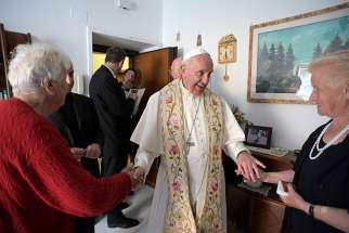 Pope Francis greets residents as he gives an Easter blessing to a home in a public housing complex in Ostia, a Rome suburb on the Mediterranean Sea, May 19. Continuing his Mercy Friday visits, the Pope blessed a dozen homes in Ostia.