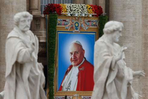 A banner depicting St. John XXIII hangs from the facade of St. Peter's Basilica at the Vatican April 27.