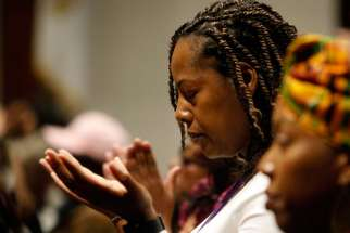 A woman prays during a healing Mass at St. Martha Church in Uniondale, N.Y.