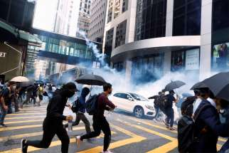 People in Hong Kong run from riot police tear gas Nov. 11, 2019.
