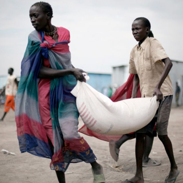 "South Sudanese who fled recent ethnic violence carry food aid from a World Food Program distribution center in Pibor, South Sudan, Jan. 12. The outbreak of violence in Jonglei state, which began in late December, has led to a ""new cycle of revenge and re taliation,"" Sudan's Council of Churches said."