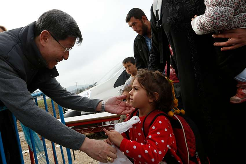 Cardinal Luis Antonio Tagle of Manila gives a food bag to a refugee family as they arrive at a transit camp in Idomeni, Greece, on the border of Macedonia Oct. 19. Thousands of refugees are arriving into Greece from Syria, Afghanistan, Iraq and other countries and then traveling further into Europe in 2015.