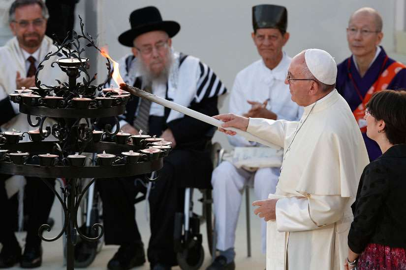 Pope Francis lights a candle during an interfaith peace gathering outside the Basilica of St. Francis in Assisi, Italy, Sept. 20. The pope and other religious leaders were attending a peace gathering marking the 30th anniversary of the first peace encounter.
