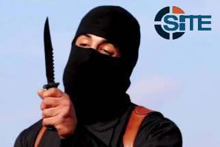 A masked, black-clad militant, identified as a Briton named Mohammed Emwazi, brandishes a knife in this still image from a 2014 video. Cardinal Vincent Nichols of Westminster planned to tell delegates at a London conference Jan. 28 to guard against the Internet recruitment of vulnerable secondary school students by the Islamic State group.